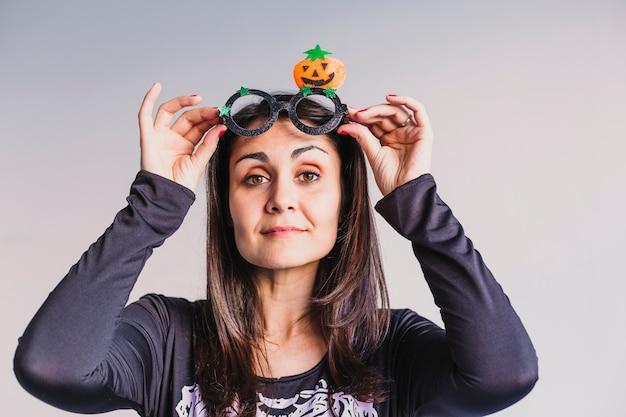 Junge frau, die lustige halloween-brille trägt und lächelt. lifestyle drinnen. skelettkostüm