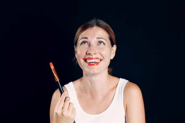Junge frau, die make-up aufträgt, malt gesicht mit malpinsel und make-up. wie man kein make-up-konzept macht.