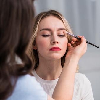 Junge frau, die make-up durch antlitzkünstler anwendet