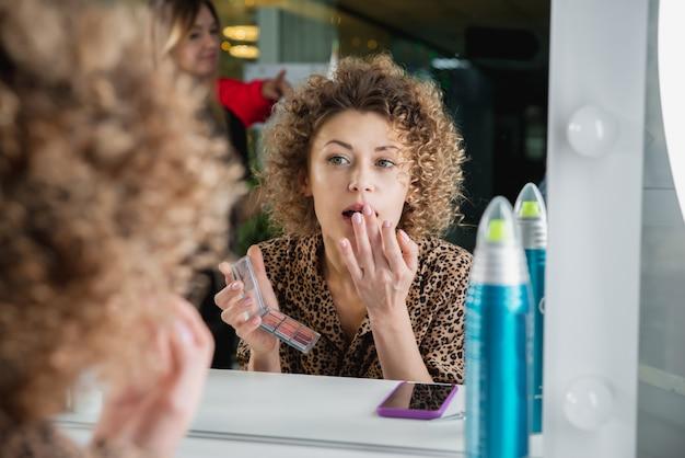 Junge frau, die make-up im schönheitssalon vor einem spiegel tut, der ihr spiegelbild betrachtet