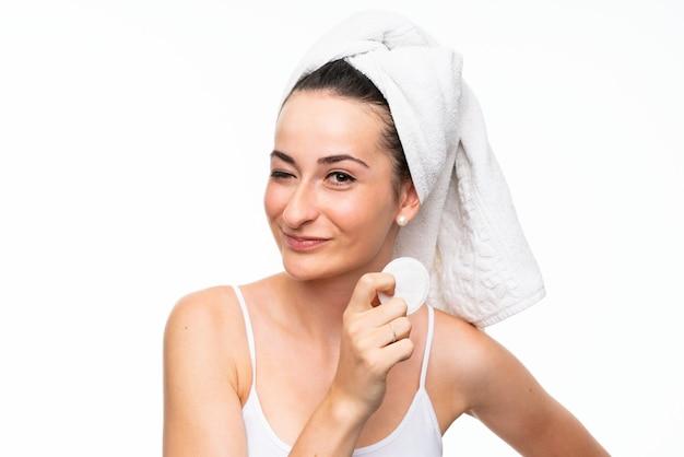 Junge frau, die make-up von ihrem gesicht mit baumwollauflage entfernt