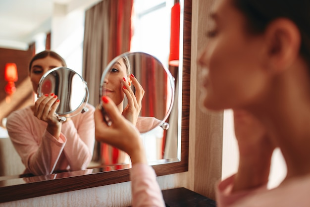 Junge frau, die make-up vor dem spiegel im schlafzimmer tut.