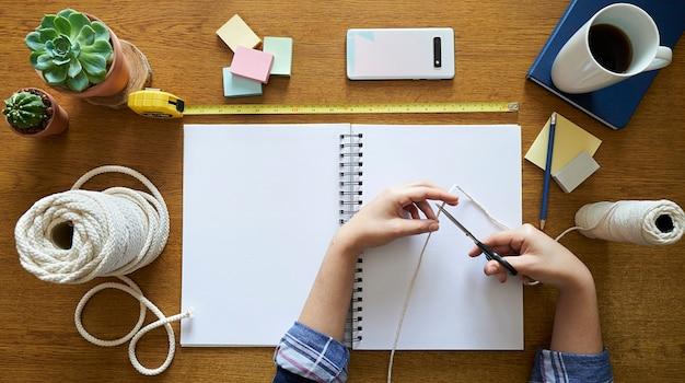 Junge frau, die makramee mit schere schneidet, um ein handgemachtes dekor auf einem hölzernen schreibtisch zu schaffen