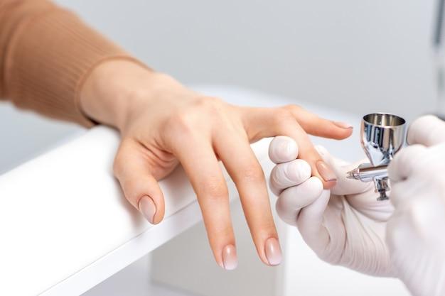 Junge frau, die maniküre durch airbrush im nagelstudio erhält. verfahren zum aufsprühen von farbe auf die nägel