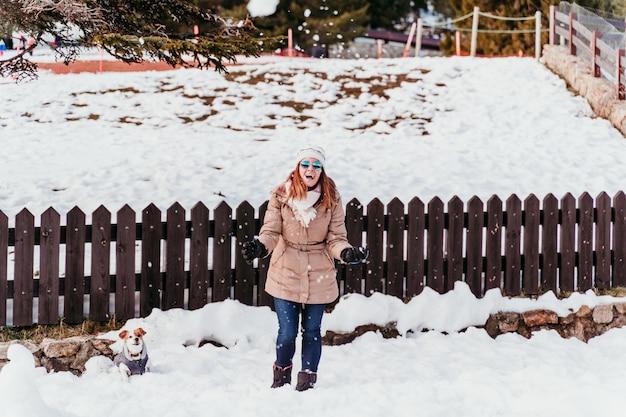 Junge frau, die mantel in der schneebedeckten hinterhofwintersaison trägt