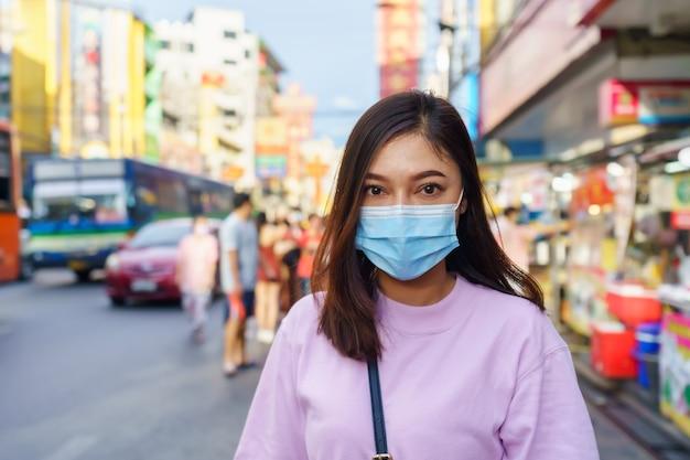 Junge frau, die maske an der yaowarat straße zur verhinderung der covid-19-viruspandemie in bangkoks chinatown trägt.