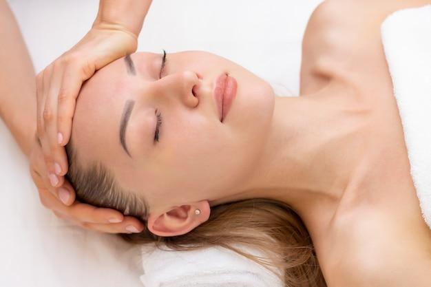 Junge frau, die massage im badekurortsalon genießt. gesichtsmassage. nahaufnahme der jungen frau badekurortmassagebehandlung am schönheitsbadekurortsalon erhalten