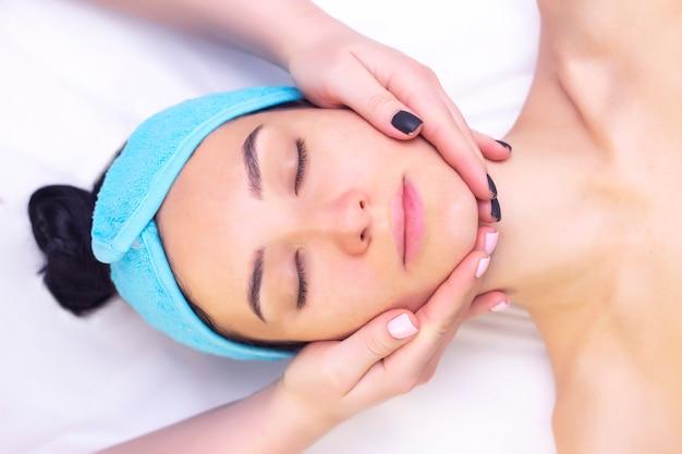 Junge frau, die massage im spa-salon genießt. gesichtsmassage. nahaufnahme der jungen frau, die spa-massagebehandlung am schönheits-spa-salon erhält.spa haut- und körperpflege. gesichtsbehandlung. kosmetologie.
