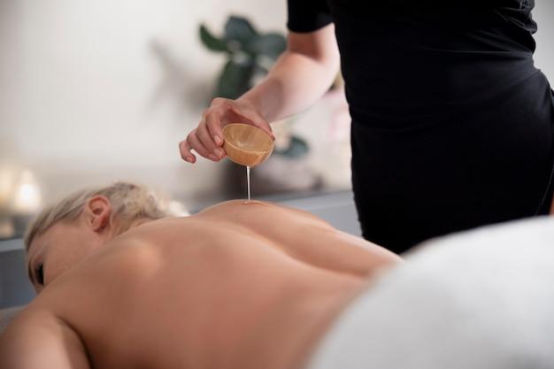 Junge frau, die massageöl auf ihrem klienten verwendet