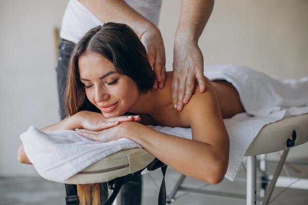 Junge frau, die masseur am kurzentrum besucht