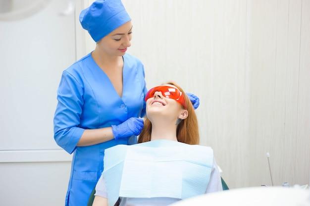 Junge frau, die medizinische überprüfung im zahnarztbüro durch den doktor hat