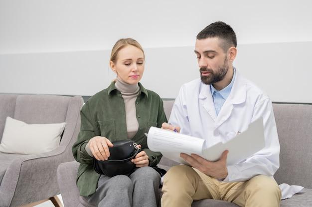 Junge frau, die medizinisches dokument betrachtet, während ihr zahnarzt fragebogen auf papier vor behandlung ausfüllt