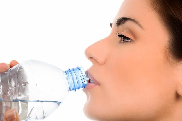 Junge frau, die mineralwasserflasche trinkt,