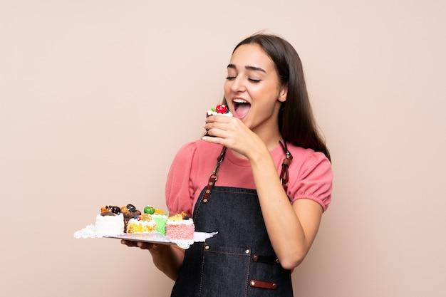 Junge frau, die minikuchen hält und es isst
