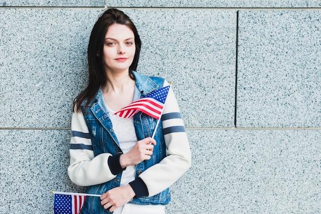 Junge frau, die mit amerikanischen flaggen aufwirft