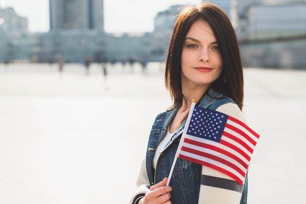 Junge frau, die mit amerikanischer flagge während des unabhängigkeitstags aufwirft