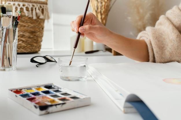 Junge frau, die mit aquarellen auf papier malt
