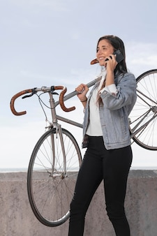 Junge frau, die mit dem telefon neben einem fahrrad spricht