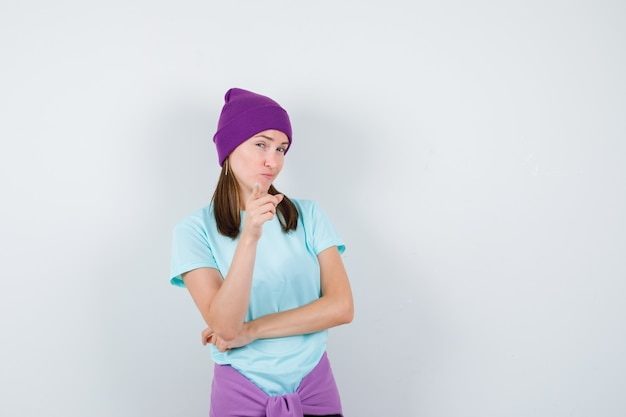 Junge frau, die mit dem zeigefinger in blauem t-shirt, lila mütze auf die kamera zeigt und neugierig aussieht, vorderansicht.