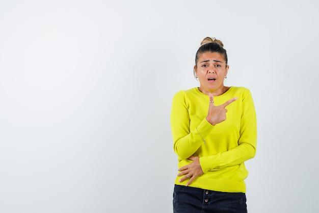 Junge frau, die mit dem zeigefinger in gelbem pullover und schwarzer hose nach rechts zeigt und gehetzt aussieht