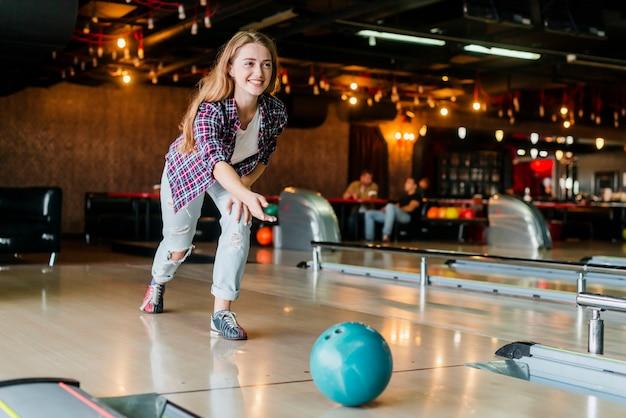 Junge frau, die mit einer bowlingkugel spielt