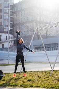 Junge frau, die mit einer kettlebell außerhalb am stadion trainiert