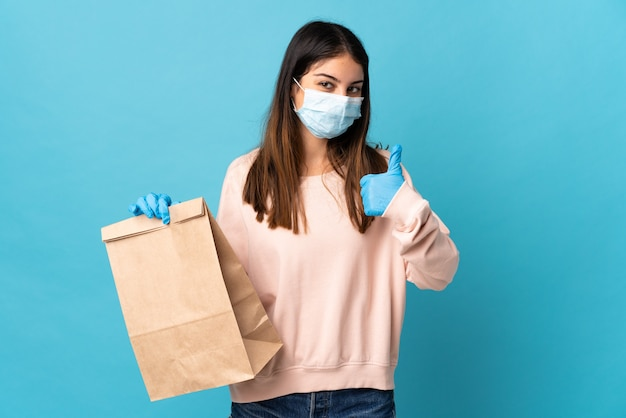 Junge frau, die mit einer maske vor dem coronavirus schützt und eine einkaufstüte hält, die auf der blauen wand mit den daumen nach oben isoliert wird, weil etwas gutes passiert ist