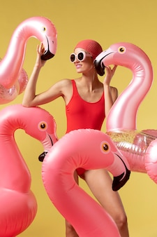 Junge frau, die mit flamingoschwimmring aufwirft