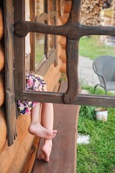 Junge frau, die mit gekreuzten beinen auf einem fensterbrett gelehnt sitzt.