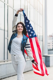 Junge frau, die mit großer amerikanischer flagge aufwirft