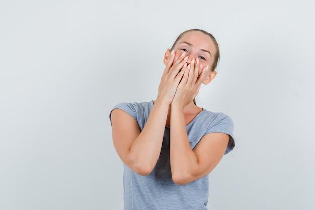 Junge frau, die mit händen auf mund in der grauen t-shirt-vorderansicht lacht.