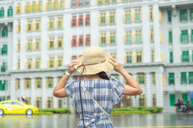Junge frau, die mit hut, glücklicher asiatischer reisenderbesuch am bunten gebäude des regenbogens in clarke quay, singapur reist. wahrzeichen und beliebt für touristische attraktionen. asien-reisekonzept