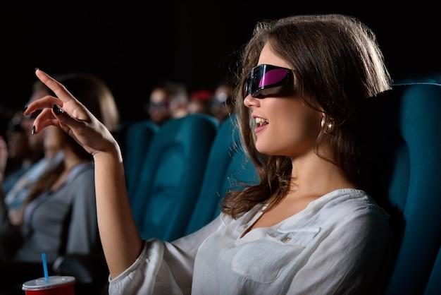 Junge frau, die mit ihrem finger auf den bildschirm zeigt, während sie einen film im kino sieht