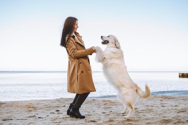 Junge frau, die mit ihrem haustier golden retriever am meer geht. hund bleibt auf zwei pfoten.