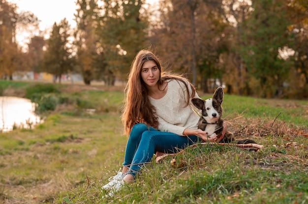 Junge frau, die mit ihrem hund am park spielt