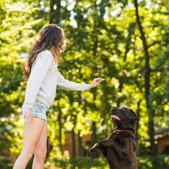 Junge frau, die mit ihrem hund im garten spielt