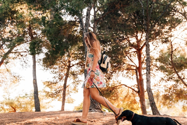 Junge frau, die mit ihrem hund im park geht