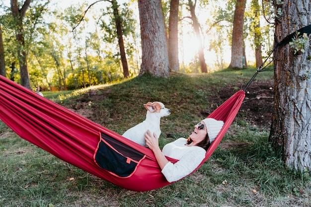 Junge frau, die mit ihrem hund in der hängematte entspannt