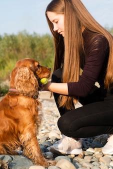 Junge frau, die mit ihrem hund spielt
