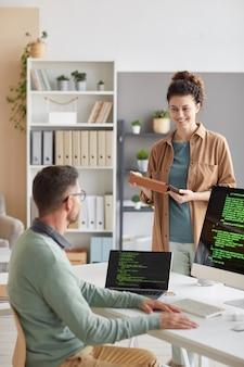 Junge frau, die mit ihrem kollegen neues computerprogramm am computer während des arbeitstages im büro bespricht