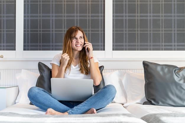 Junge frau, die mit ihrem laptop auf dem bett sitzt und mit einer geste der freude am telefon spricht oder etwas erreicht hat