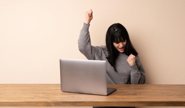 Junge frau, die mit ihrem laptop feiert einen sieg arbeitet