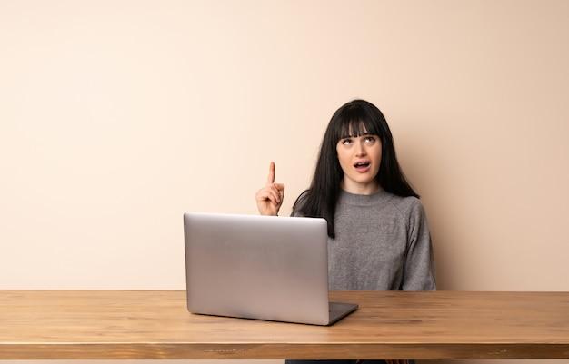 Junge frau, die mit ihrem laptop oben zeigt und überrascht arbeitet