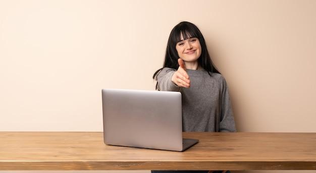 Junge frau, die mit ihrem laptop rüttelt hände für das schließen viel arbeitet