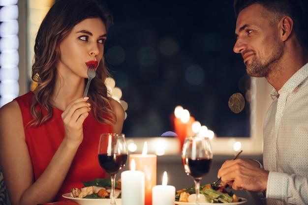 Junge frau, die mit ihrem mann isst und flirtet, während sie romantisches abendessen haben