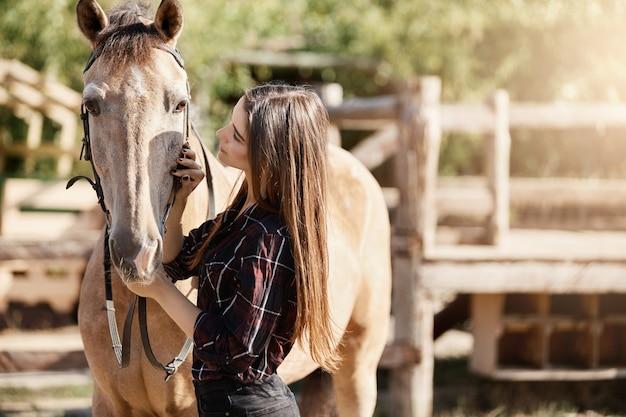 Junge frau, die mit ihrem pferd auf einer ranch spricht. gute karrieremöglichkeiten im freien mit tieren.