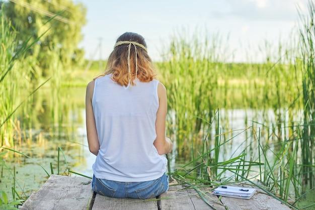 Junge frau, die mit ihrem rücken auf hölzernem pier sitzt, malerischen blick auf seewasser genießt, sich in der natur am sonnigen sommertag entspannt, raum kopiert