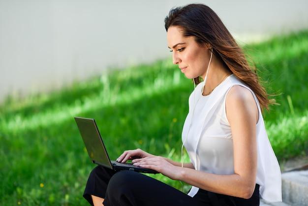 Junge frau, die mit ihrer laptop-computer sitzt auf dem boden arbeitet.
