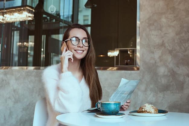 Junge frau, die mit kaffee- und hörnchenlesung frühstückt