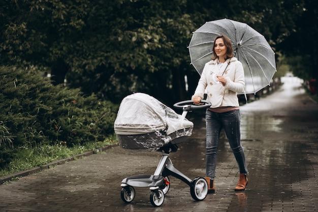 Junge frau, die mit kinderwagen unter dem regenschirm in einem regnerischen wetter geht